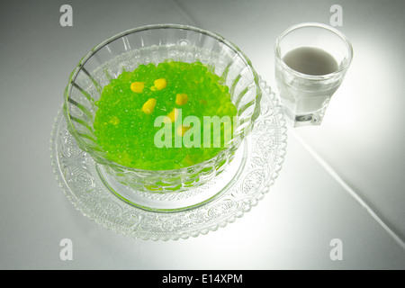 Thai Sago Sagu Pudding green pearls with corn yellow seeds [served warm] coconut milk tumbler crystal glass saucer - Stock Photo