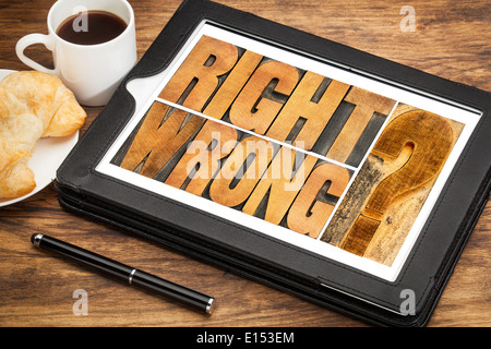 right or wrong ethical choice dilemma - word abstract in wood letterpress printing blocks on a digital tablet - Stock Photo