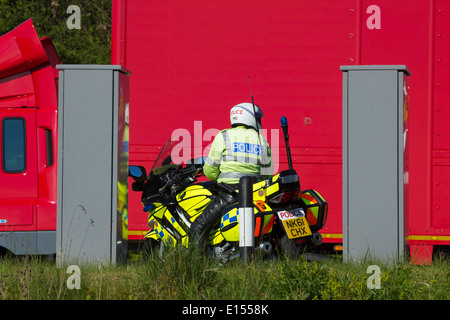 Police motorcycle in layby on Dual Carriageway with Royal Mail truck passing - Stock Photo