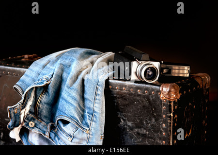 Pair of jeans and old movie camera on a vintage suitcase - Stock Photo