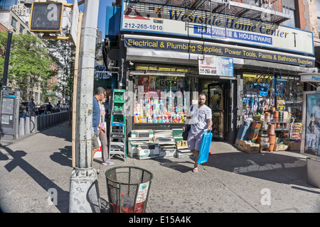street corner scene outside houseware store with merchandise piled on the sidewalk in Hells Kitchen neighborhood - Stock Photo