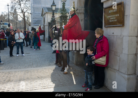 Woman and child posing next to a mounted member of the Household Cavalry, Life Guards Regiment, Horse Guards Parade, - Stock Photo