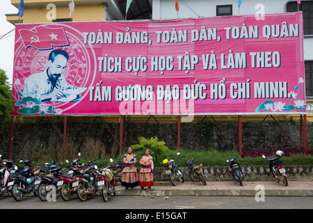 Two Flower Hmong women standing in from of a large propaganda billboard featuring Ho Chi Minh outside of Bac Ha - Stock Photo