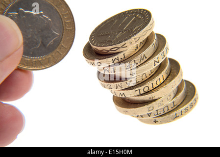 pile of pound coins with a hand holding a two pound coin - Stock Photo