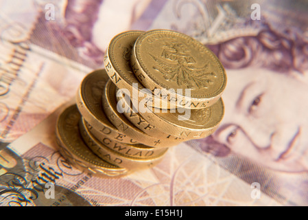 a pile of pound coins and some twenty pound notes - Stock Photo