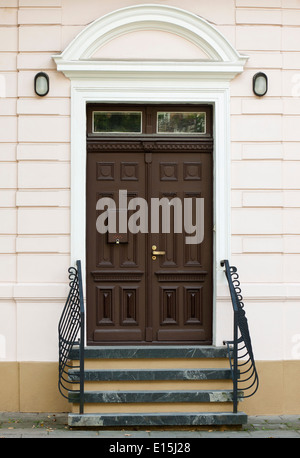 Front door of old house and decorative metal handrail - Stock Photo