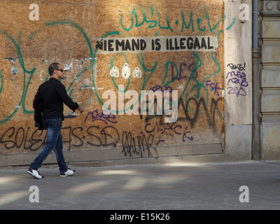Man walking in a street with graffiti saying nobody is illegal in Dutch language, Brussels, Belgium - Stock Photo