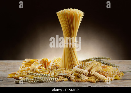 variety of uncooked pasta on wooden table with ears of wheat - Stock Photo