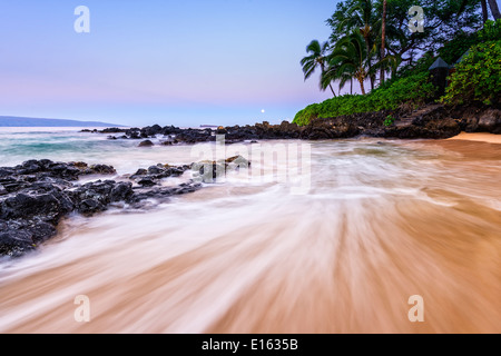 Sunrise with the Moon over beautiful and secluded Secret Beach in Maui, Hawaii. - Stock Photo