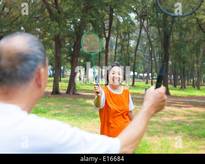 senior couple or friends playing badminton in the park - Stock Photo