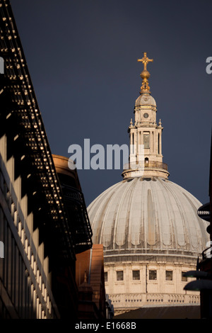 St Paul's Cathedral dome seen between buildings along street in dramatic storm light with dark sky City of London - Stock Photo