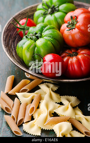 Fresh green and red tomatoes with mixed pasta - Stock Photo