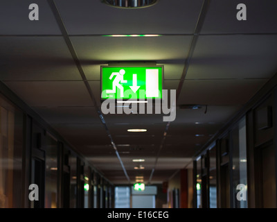 Green lit emergency exit sign in ceiling of dark corridor, this way out - Stock Photo
