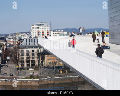 Tourists enjoying the view from the roof of the Opera in Oslo Norway, surroundings reflected in the glass facade - Stock Photo