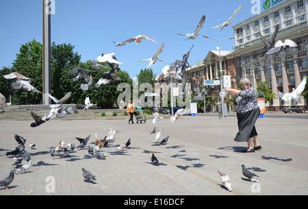 Donetsk, Ukraine. 24th May, 2014. A woman feeds pigeons at Lenin Square in Donetsk, Donetsk region, Ukraine, May - Stock Photo