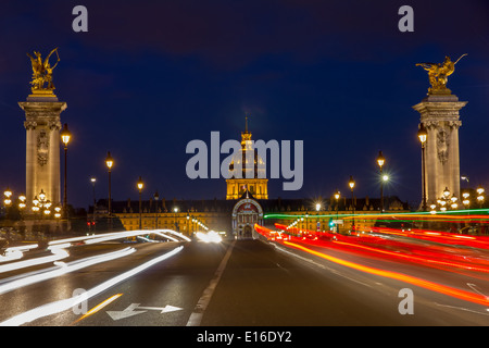 Pont Alexandre III and Les Invalides at night illumination in Paris, France - Stock Photo
