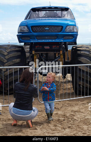 Mum taking photo of toddler in front of Bigfoot monster truck on the first day of the first ever Bournemouth Wheels - Stock Photo