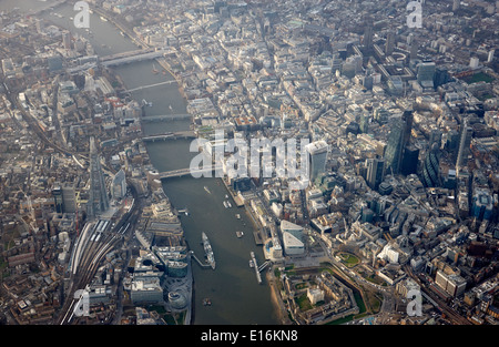 aerial view through aircraft window looking down upon city of London financial district and river thames centre - Stock Photo