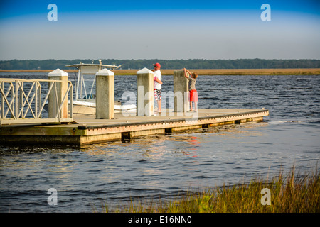 A patriotically dressed man and his son wait on the dock for the ferry boat destined for Cumberland Island National - Stock Photo