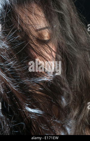 Beautiful young woman hair covering face - Stock Photo
