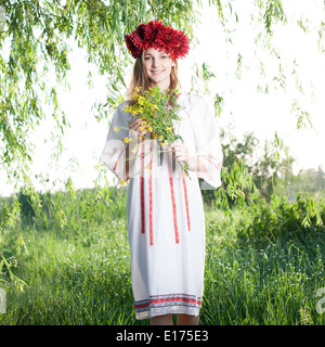 Young woman posing in traditional ukrainian costume outdoors - Stock Photo