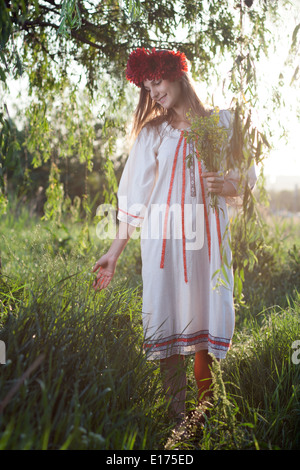 Ukrainian girl walks in the green grass - Stock Photo