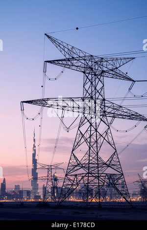Electricity transmission lines and pylons and skyline at dusk in Dubai United Arab Emirates - Stock Photo