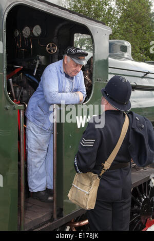 WWII train at Ramsbottom, Lancashire, UK. 25th May, 2014.  British waretime Police and steam Train driver at the - Stock Photo