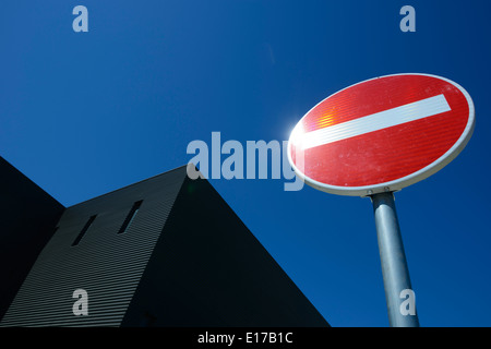 No entry road sign against a clear blue sky - Stock Photo