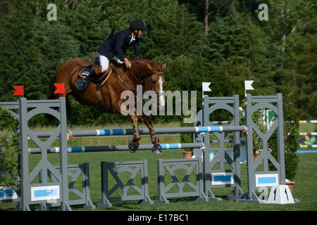 Rider on horse jumping over obstacle during an equestrian competition - Stock Photo