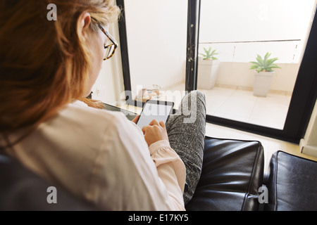 Over the shoulder view of young lady sitting on couch using digital tablet at her apartment. Female reading e-book. - Stock Photo