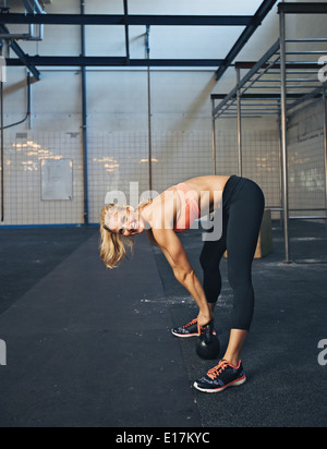 Female fitness model exercising with kettle bell at gym. Happy young caucasian woman doing crossfit workout. - Stock Photo