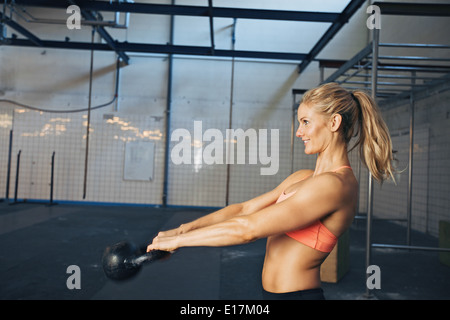 Side view of happy young woman exercising with kettle bell at gym. Caucasian female athlete doing crossfit workout - Stock Photo