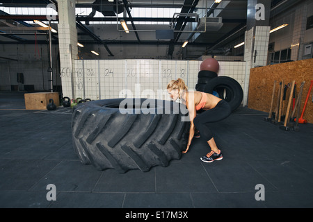 Tough female athlete flipping a huge tire. Young woman doing crossfit exercise at gym. - Stock Photo