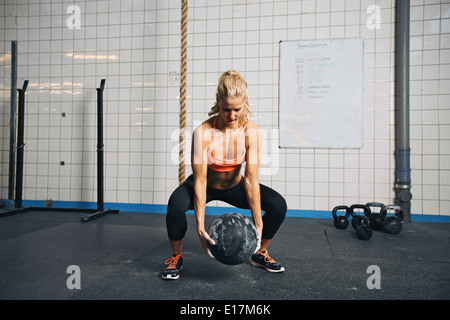 Fit and strong female athlete working out with a medicine ball to get better core strength and stability. Woman - Stock Photo