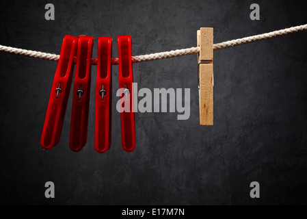 Clothes pins on the rope. Wooden one is Standing out from the crowd. - Stock Photo
