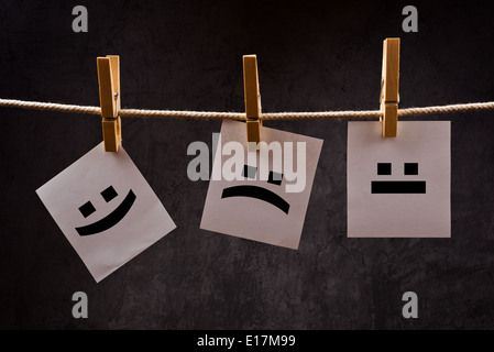 Emoticons printed on note paper attched to rope with clothes pins - happy, sad and neutral. - Stock Photo