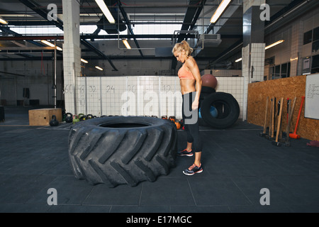 Strong young woman athlete standing and looking at huge tire at gym. Fit female athlete performing tire flipping - Stock Photo