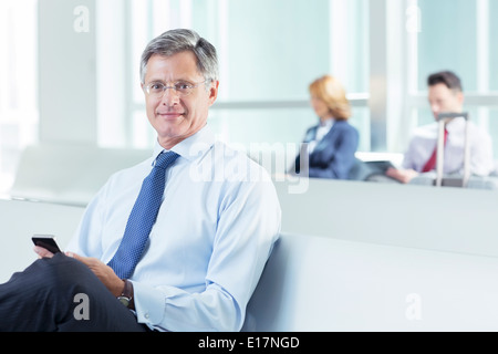 Portrait of businessman texting at airport - Stock Photo