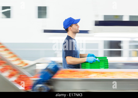 Worker carrying crate in food processing plant - Stock Photo