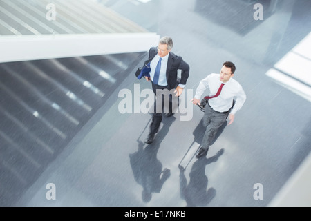 Businessmen with suitcases running in lobby - Stock Photo