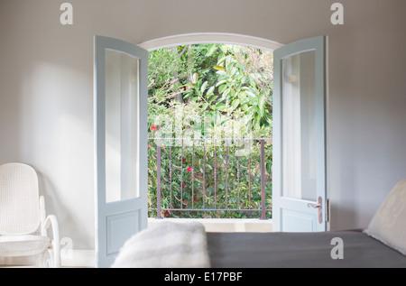 French doors open to balcony in luxury bedroom - Stock Photo
