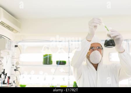Scientist in clean suit conducting scientific experiment in laboratory - Stock Photo