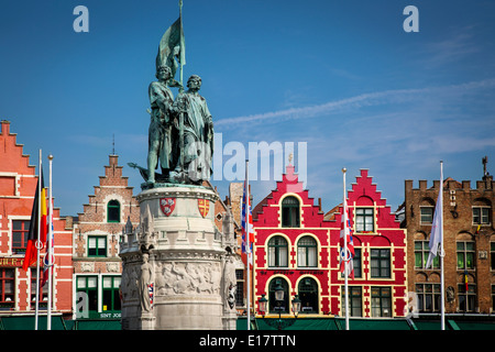 Statue of Jan Breydel and Pieter de Coninck and the Buildings of the Market Square in medieval town of Bruges, West - Stock Photo