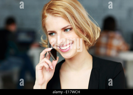 Cheerful blonde businesswoman talking on the phone in office - Stock Photo