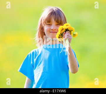 Boy Holding a Bunch of Dandelions in a Spring Meadow - Stock Photo