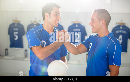 Soccer players shaking hands in locker room - Stock Photo