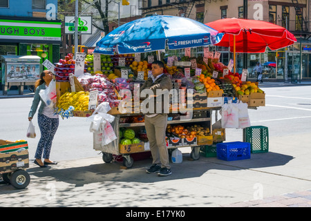 Fruit and vegetable cart with umbrellas on a street in New York City - Stock Photo