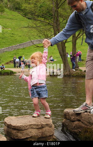 A family crosses the stepping stones of the River Dove at Dovedale in the Manifold Valley,Peak District, Derbyshire, - Stock Photo