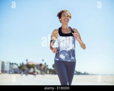 Woman running on beach - Stock Photo